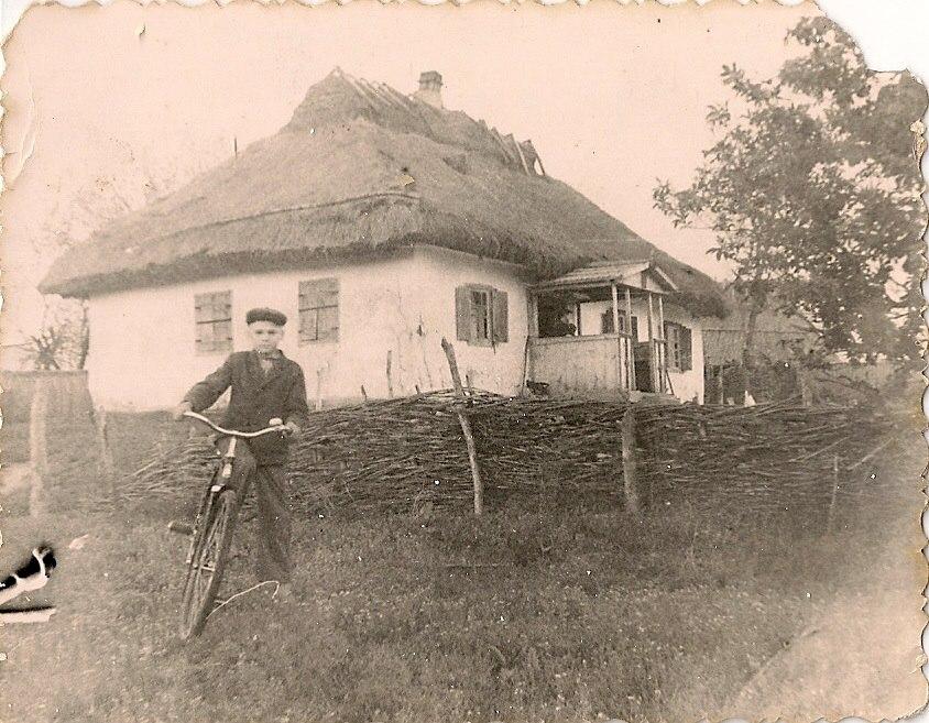 Фото з будинку Науменко (Дивнич – дівоче) Мотрі Павлівни (1925 р.н.). с. Розсошинці Чигиринського району. Хлопець на велосипеді на тлі хати під соломою.